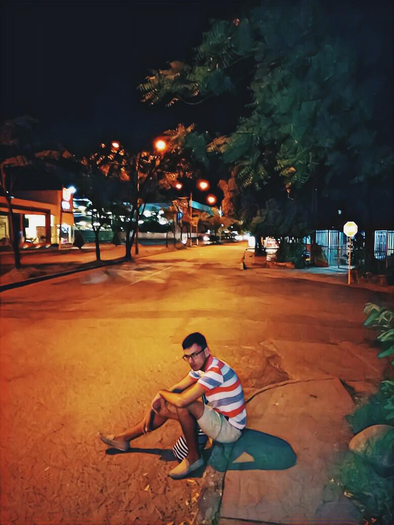 Chico sentado en la acera de una calle de Neiva Colombia
