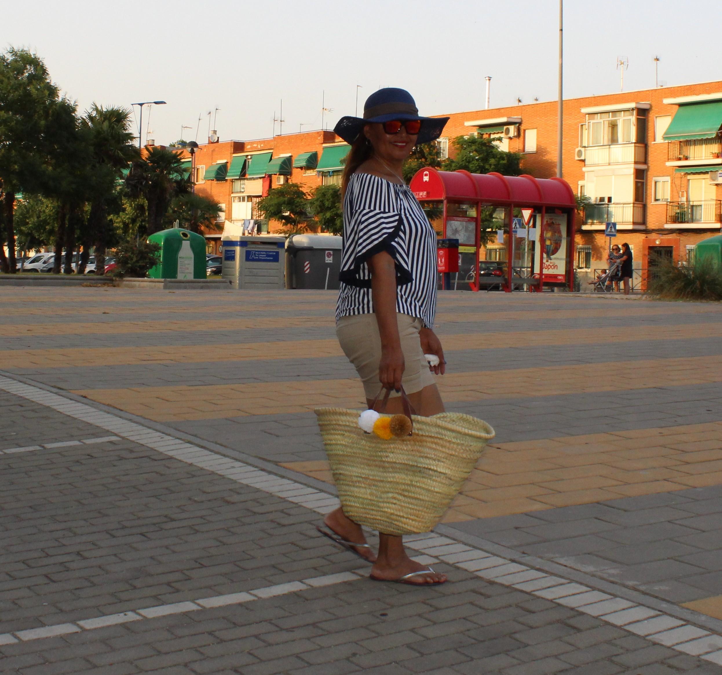 Look de verano compuesto Por: Pamela azul, gafas espejo rojo, cesta de rafia con pompones, blusa escote de barco y pantalon corto.