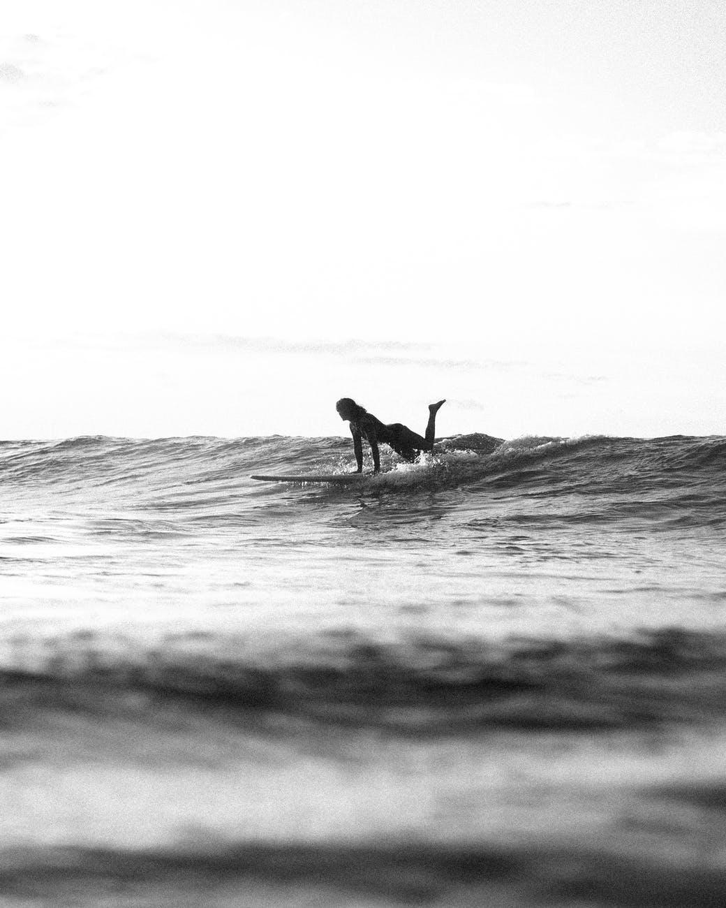 silhouette of woman on surfboard in water