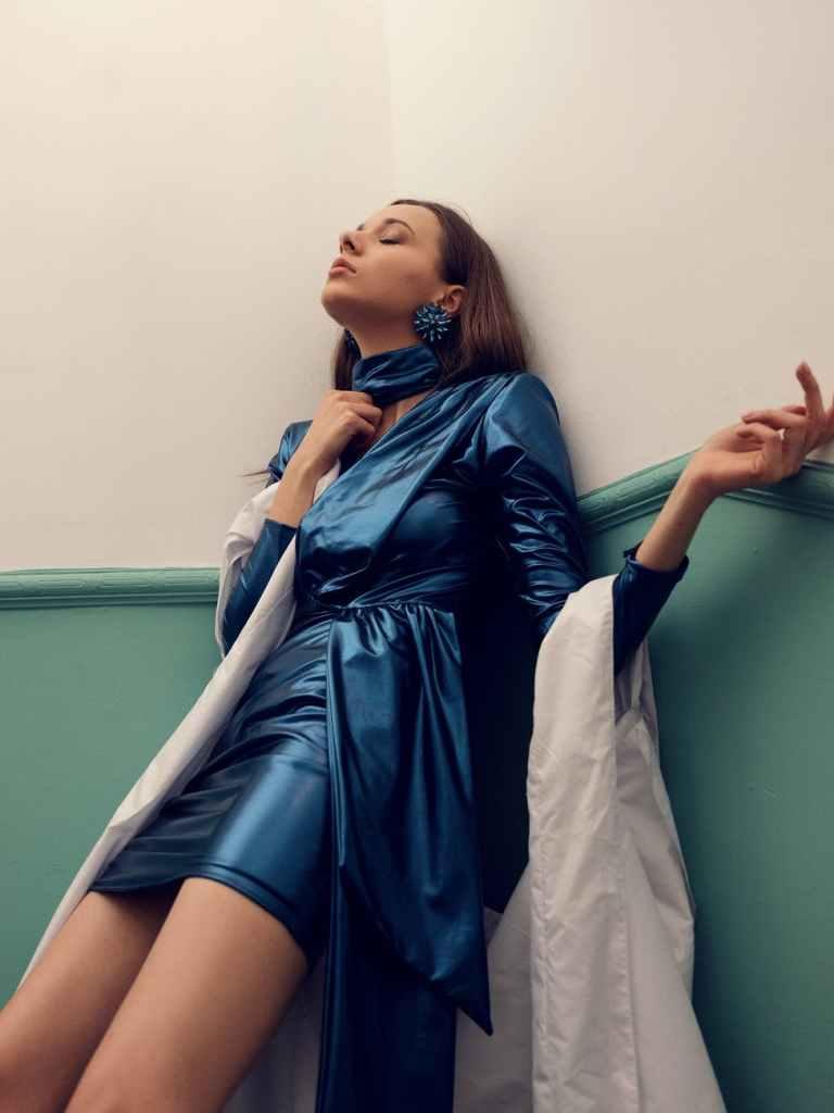 woman in blue long sleeve dress leaning on wall