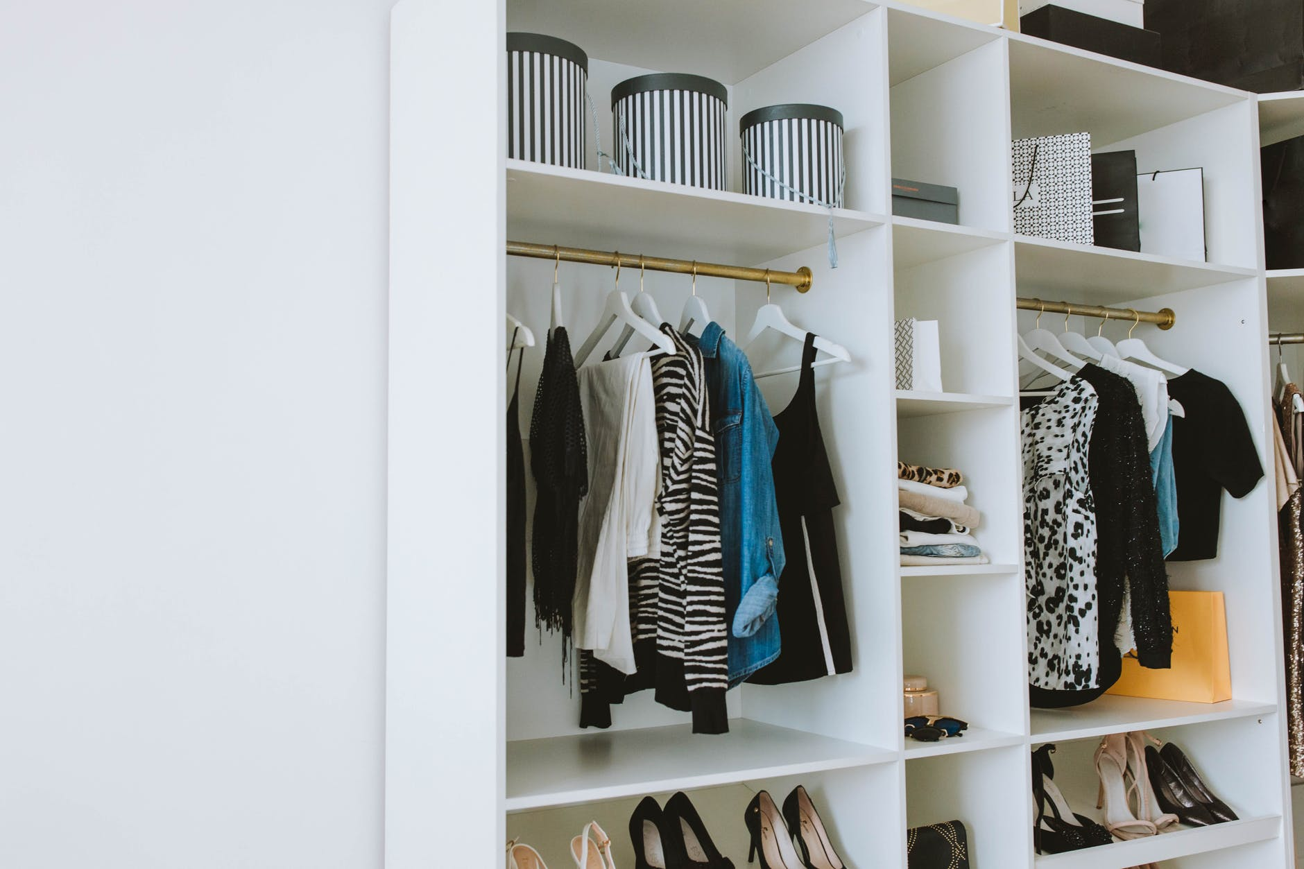 clothes hanged on white wooden cabinet